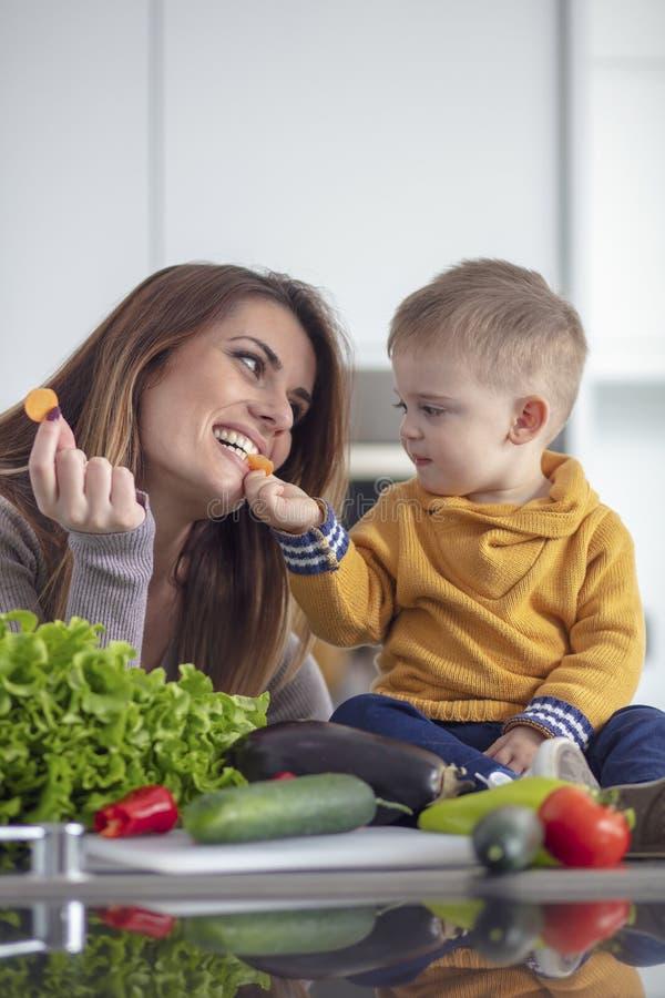 Familia feliz que prepara verduras juntas en casa en la cocina fotos de archivo