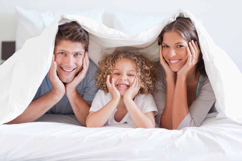 Familia feliz que presenta bajo un duvet fotografía de archivo