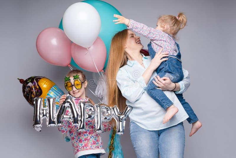 Familia feliz que presenta mientras que celebra la fiesta de cumpleaños fotografía de archivo