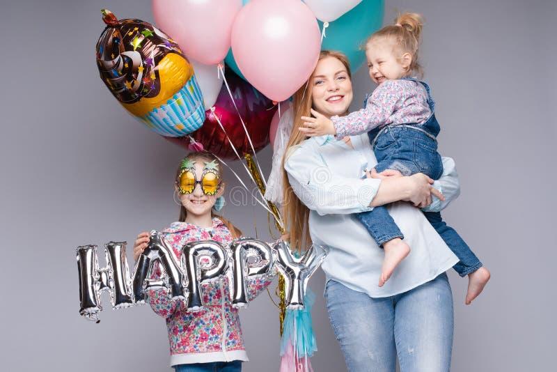 Familia feliz que presenta mientras que celebra la fiesta de cumpleaños fotografía de archivo libre de regalías