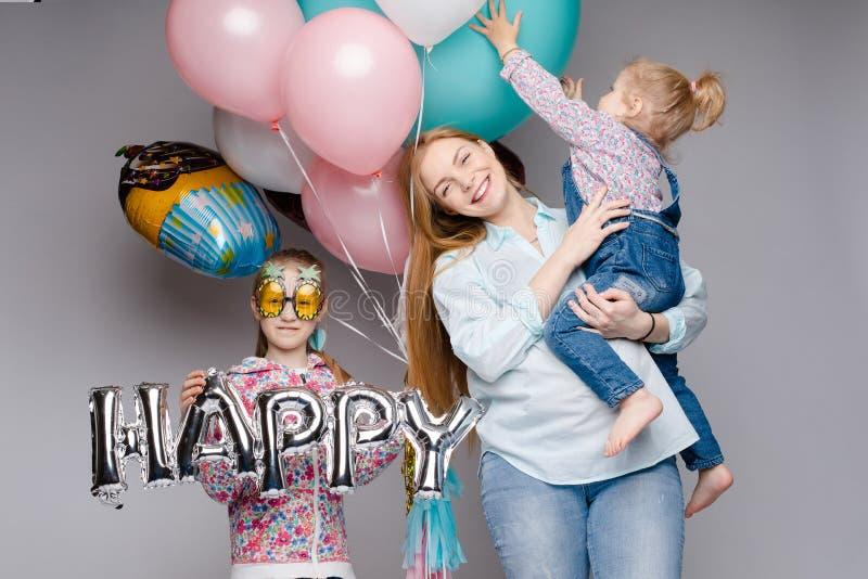 Familia feliz que presenta mientras que celebra la fiesta de cumpleaños fotos de archivo libres de regalías