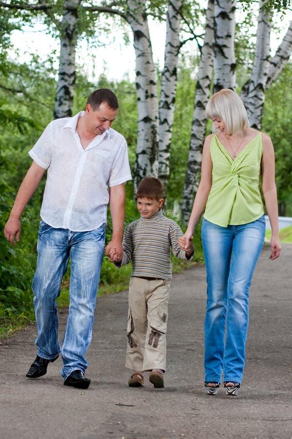 Familia feliz que recorre en el parque foto de archivo