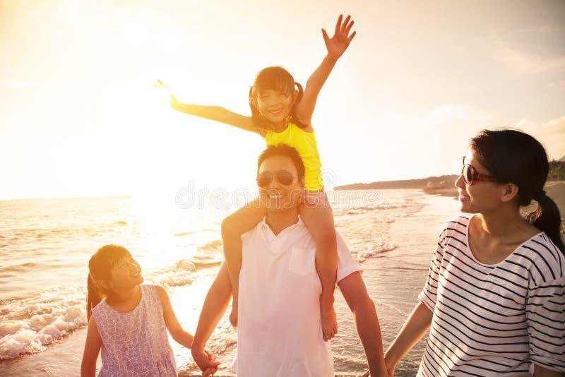 Familia feliz que recorre en la playa imágenes de archivo libres de regalías