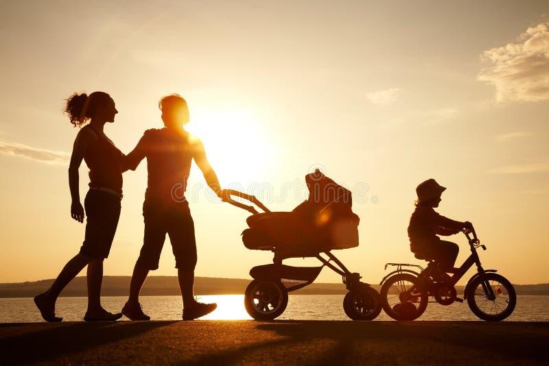 Familia feliz que recorre en puesta del sol foto de archivo