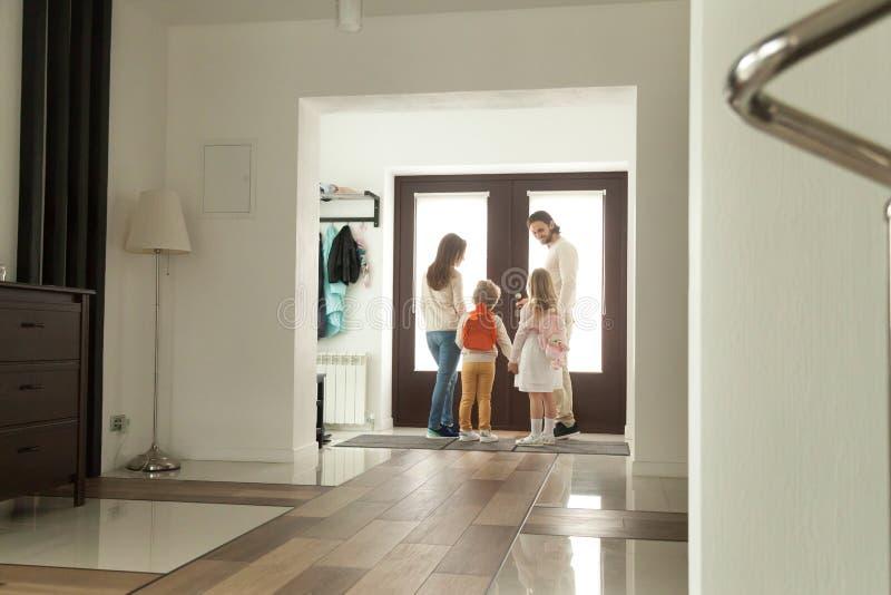 Familia feliz que sale junto, padres que se van a casa con los niños fotografía de archivo libre de regalías