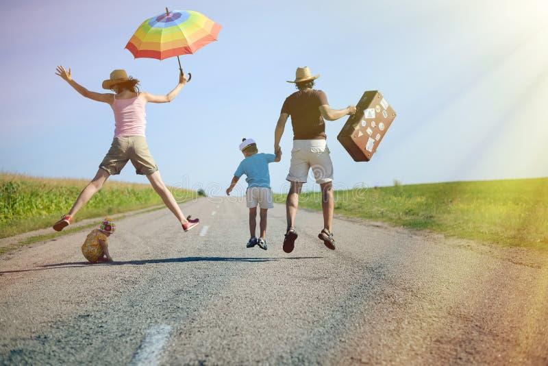 Familia feliz que salta con la maleta en la carretera nacional imagenes de archivo