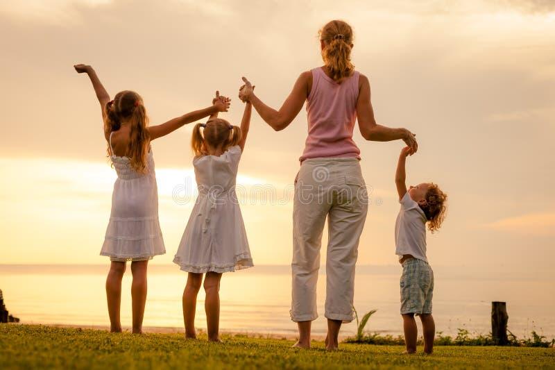 Familia feliz que salta en la playa fotos de archivo