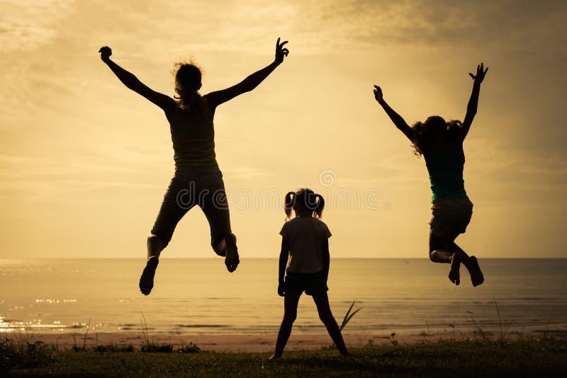 Familia feliz que salta en la playa imágenes de archivo libres de regalías