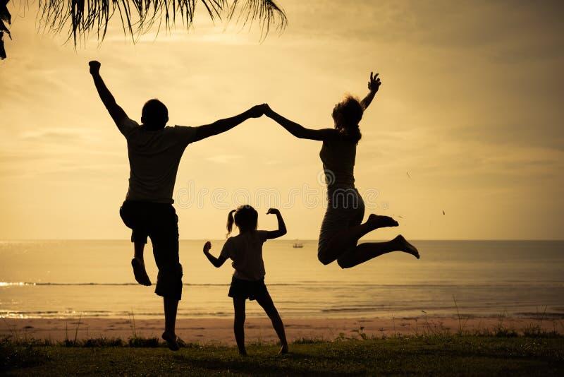 Familia feliz que salta en la playa en el tiempo del amanecer imagenes de archivo