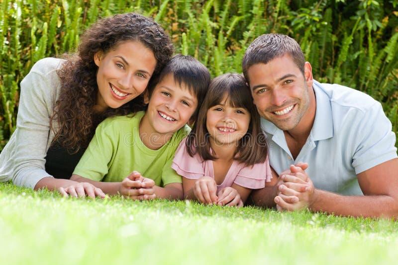 Familia feliz que se acuesta en el jardín