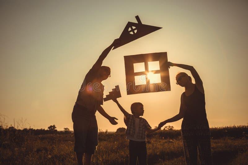 Familia feliz que se coloca en el campo en el tiempo de la puesta del sol foto de archivo libre de regalías