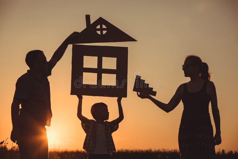 Familia feliz que se coloca en el campo en el tiempo de la puesta del sol imagen de archivo