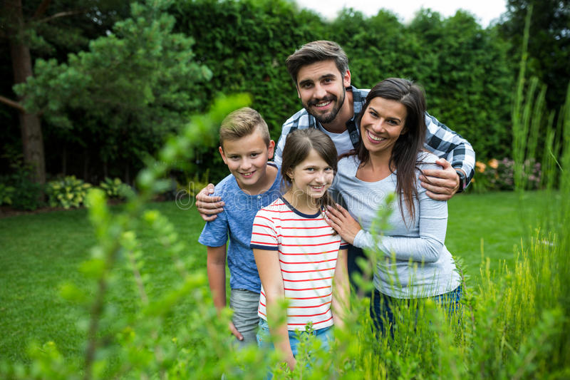 Familia feliz que se coloca en hierba en parque en un día soleado fotografía de archivo libre de regalías