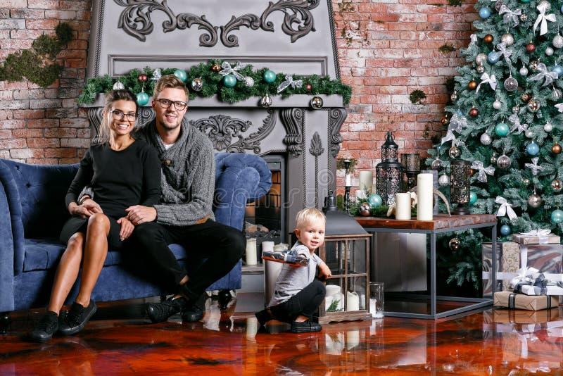 Familia feliz que se divierte en el país Mañana de la Navidad en sitio del desván con la pared de ladrillo Padres jovenes con el  foto de archivo libre de regalías