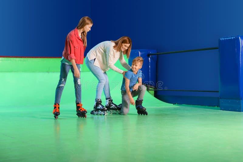 Familia feliz que se divierte en la pista del rodillo imagenes de archivo