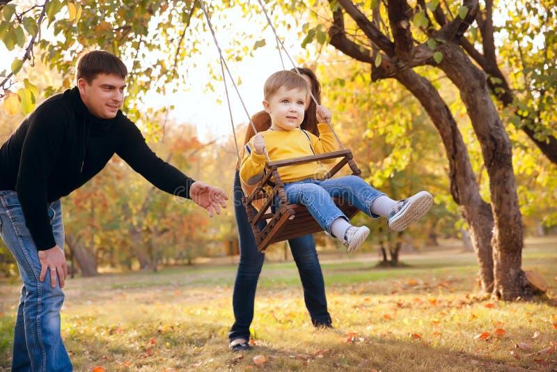 Familia feliz que se divierte en un paseo del oscilación en un jardín al día del otoño imagenes de archivo