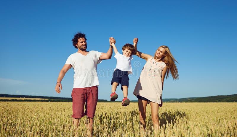 Familia feliz que se divierte que juega en el campo imagen de archivo libre de regalías