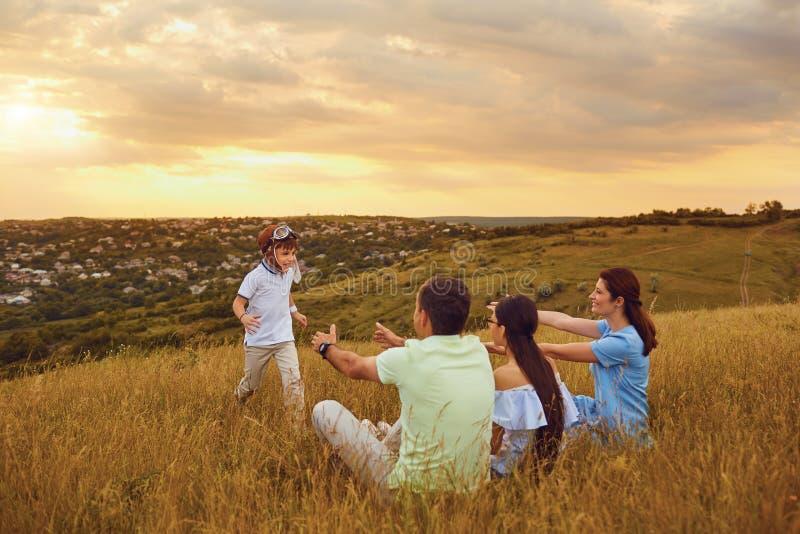 Familia feliz que se divierte que juega en hierba en naturaleza imágenes de archivo libres de regalías