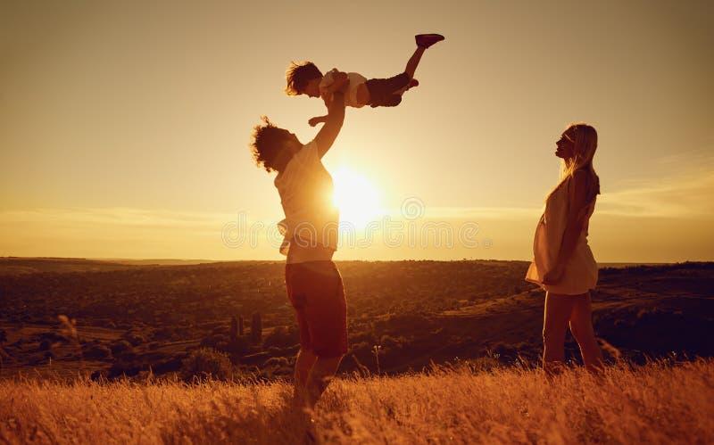 Familia feliz que se divierte que juega en la puesta del sol en la naturaleza imagen de archivo libre de regalías