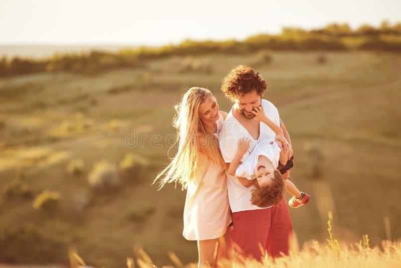 Familia feliz que se divierte que juega en la puesta del sol en naturaleza fotos de archivo libres de regalías