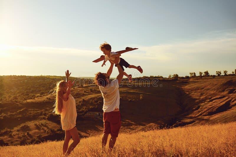 Familia feliz que se divierte que juega en la puesta del sol fotos de archivo libres de regalías