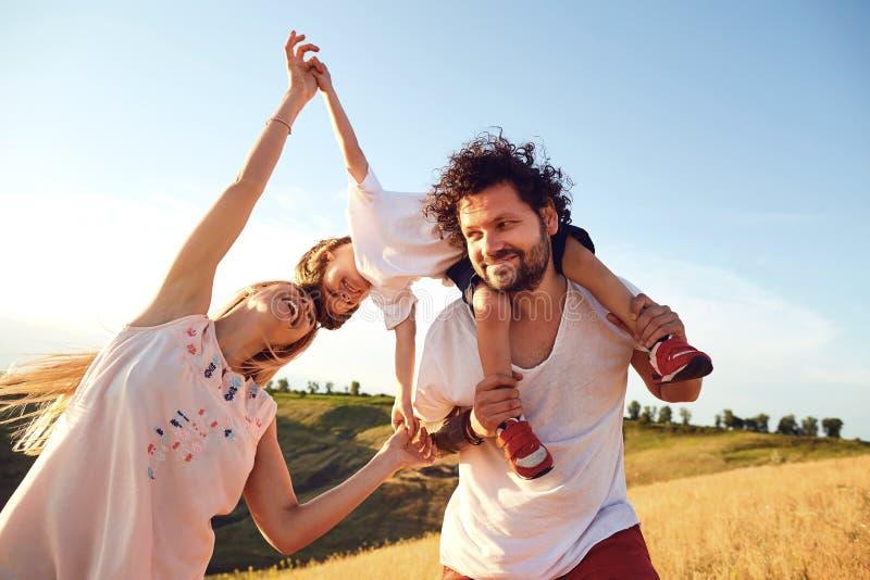 Familia feliz que se divierte que juega en naturaleza fotos de archivo libres de regalías