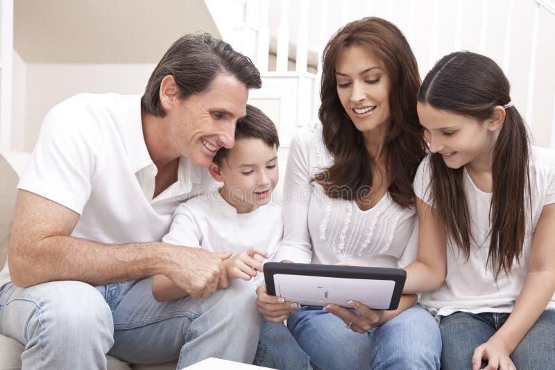 Familia feliz que se divierte usando el ordenador de la tablilla imagenes de archivo