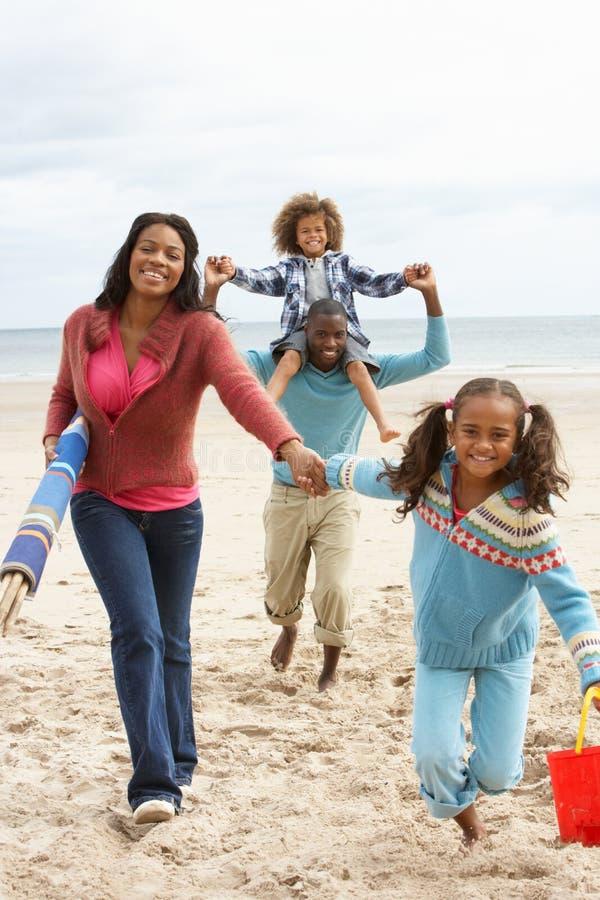 Familia feliz que se ejecuta en la playa imagenes de archivo