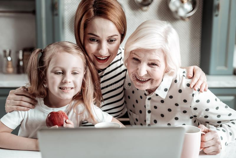 Familia feliz que se inclina al ordenador portátil y que sonríe mientras que comunica con los parientes imagenes de archivo
