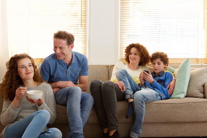 Familia feliz que se sienta en casa imágenes de archivo libres de regalías