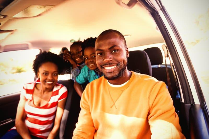 Familia feliz que se sienta en coche fotografía de archivo libre de regalías