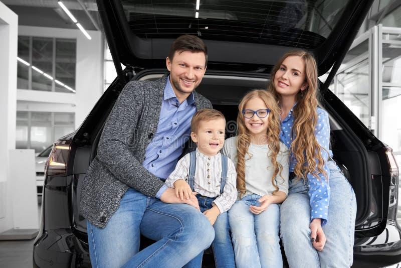 Familia feliz que se sienta en el espacio del equipaje del coche, presentando imagenes de archivo