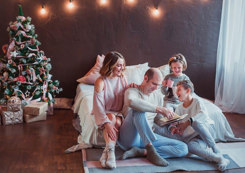 Familia feliz que se sienta en el piso por la cama en el interior del Año Nuevo El papá está leyendo un libro Risa de los niños S fotos de archivo libres de regalías
