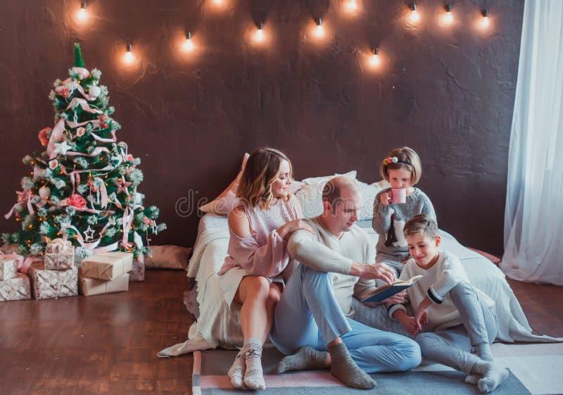 Familia feliz que se sienta en el piso por la cama en el interior del Año Nuevo El papá está leyendo un libro Risa de los niños S imagenes de archivo