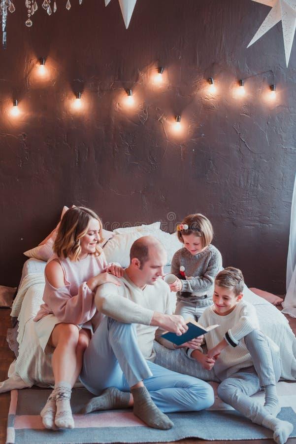 Familia feliz que se sienta en el piso por la cama en el interior del Año Nuevo El papá está leyendo un libro Risa de los niños S fotografía de archivo