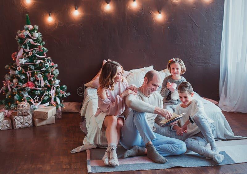 Familia feliz que se sienta en el piso por la cama en el interior del Año Nuevo El papá está leyendo un libro Risa de los niños S imagen de archivo libre de regalías