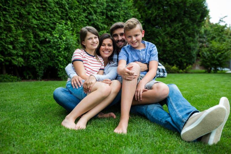 Familia feliz que se sienta en hierba en parque en un día soleado foto de archivo