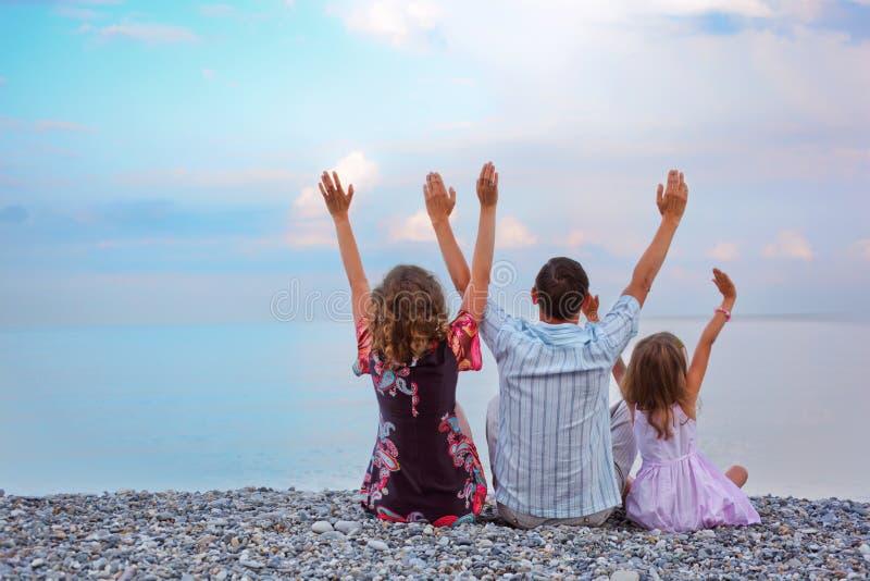 Familia feliz que se sienta en la mano levantada playa foto de archivo libre de regalías