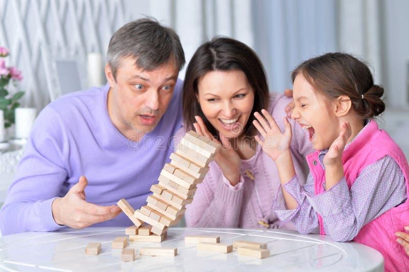 Familia feliz que se sienta en la tabla y que juega con los bloques de madera fotografía de archivo