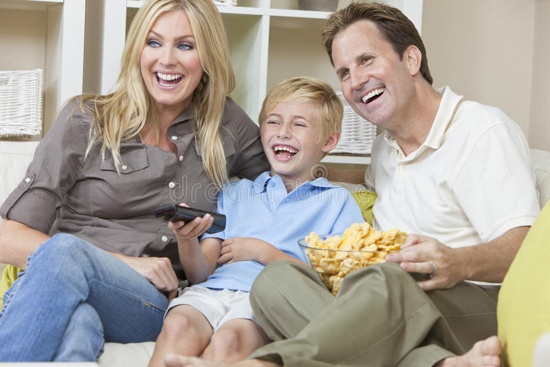 Familia feliz que se sienta en la televisión de observación del sofá fotos de archivo