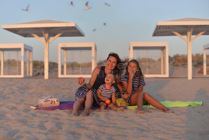 Familia feliz que se sienta en las toallas en la playa arenosa imagenes de archivo