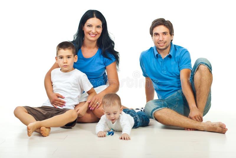 Familia feliz que se sienta en suelo fotografía de archivo