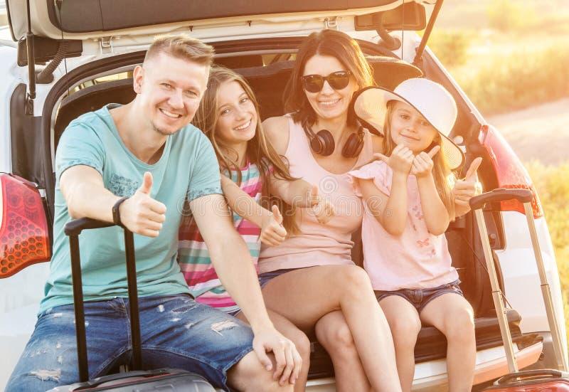 Familia feliz que se sienta en un tronco de un coche con en vacaciones del viaje foto de archivo libre de regalías