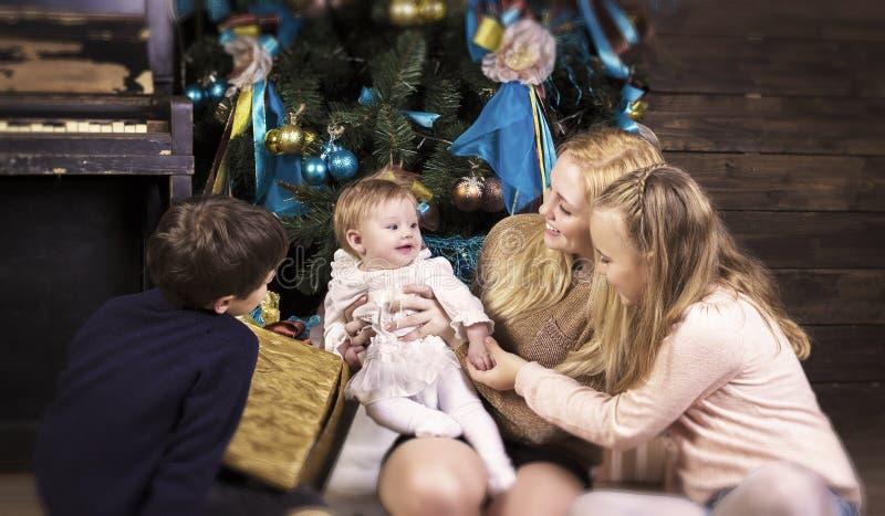 Familia feliz que se sienta por el árbol de navidad fotos de archivo