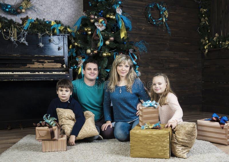Familia feliz que se sienta por el árbol de navidad imagenes de archivo