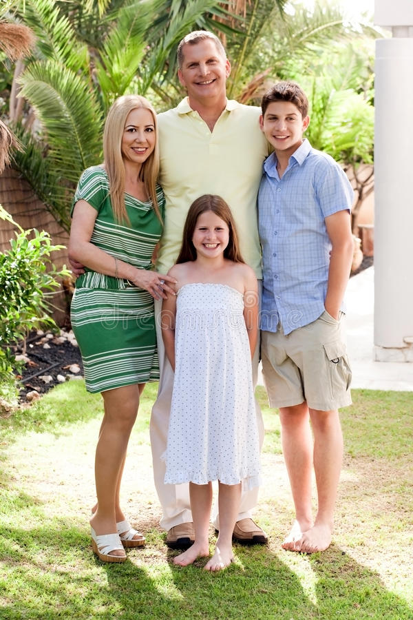 Familia feliz que se une en su patio trasero imagen de archivo