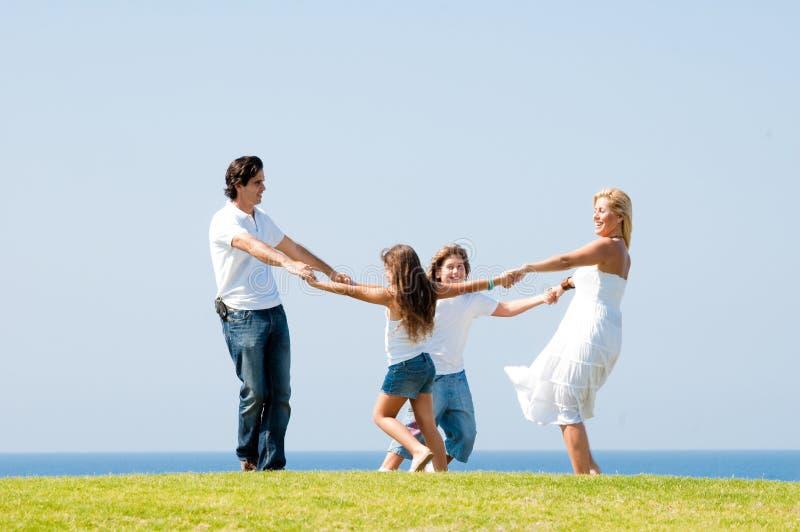 Familia feliz que sonríe y que se divierte al aire libre fotografía de archivo libre de regalías