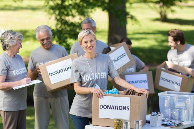 Familia feliz que sostiene las cajas de las donaciones imagenes de archivo