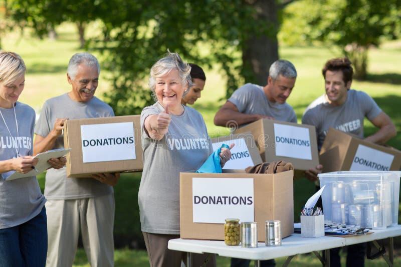Familia feliz que sostiene las cajas de las donaciones con el pulgar para arriba fotografía de archivo