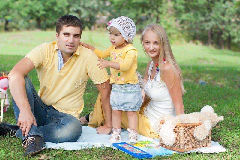 Familia feliz que tiene comida campestre en parque. foto de archivo